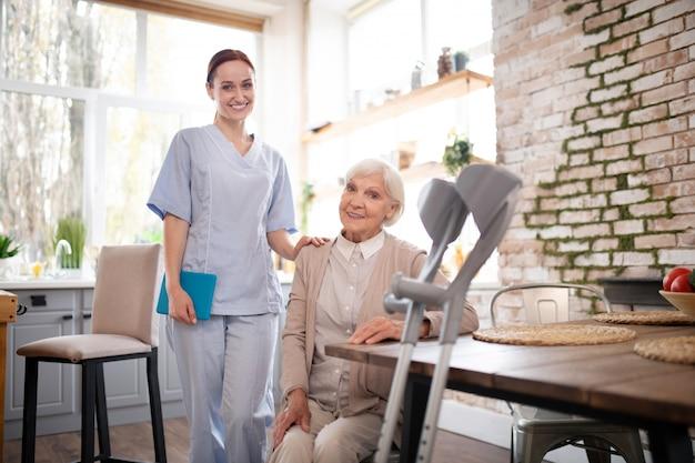 Rentnerin sitzt am tisch in der nähe ihrer angenehmen krankenschwester