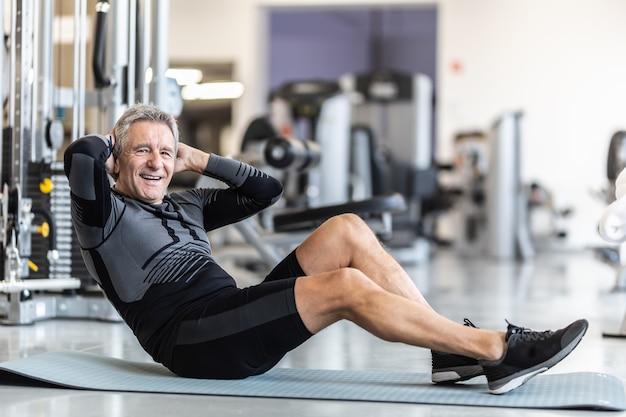 Rentnermann bleibt fit, indem er situps in einem fitnessstudio macht.