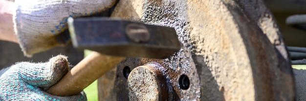 Reparatur der autotrommelbremse durch behandschuhte hände der männer. zerlegt eine verklemmte scheibe mit einem hammer. reparatur einer kaputten trommelbremse im freien zerlegt. banner