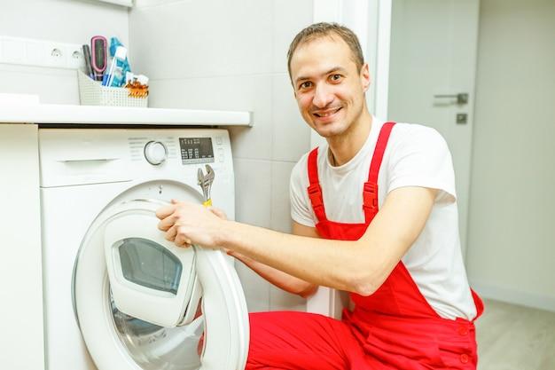 Reparatur der waschmaschine. reparateurhände mit dem schraubenzieher, der beschädigtes gerät zur reparatur zerlegt
