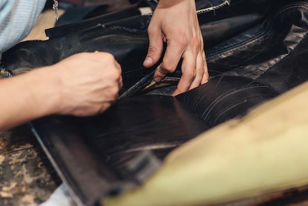 Reparatur des alten autositzes. die hände des automechanikers verwenden werkzeuge. arbeitshände eines mannes beim autoservice, nahaufnahme.