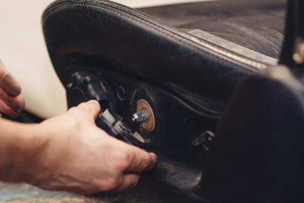 Reparatur des alten autositzes. die hände des automechanikers verwenden werkzeuge.