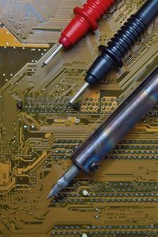 Reparatur des computer-motherboards. lötkolben und zange über dem mikrokreislauf.