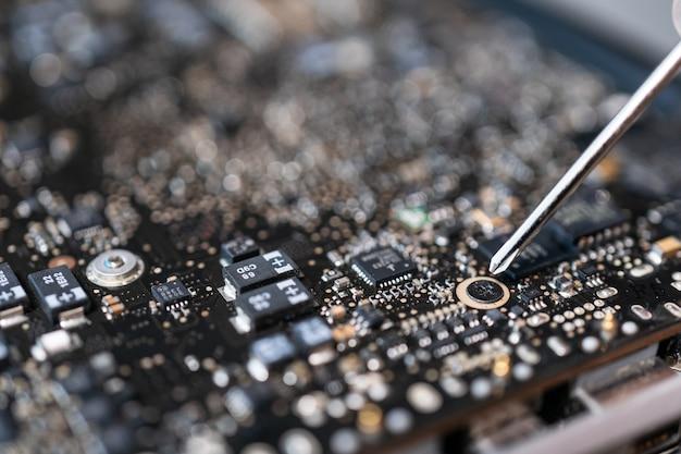 Reparatur eines kaputten laptop-mainboards, techniker mit schraubendreher.