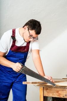 Reparatur-, heimwerker- und renovierungskonzept. zimmermann in blauen overalls, der mit einer handsäge ein brett sägt