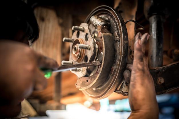 Reparatur oder inspektion von bremsen von bremssystemen und austausch neuer bremsbeläge durch mechaniker, die in autowerkstätten die bremsbeläge wechseln
