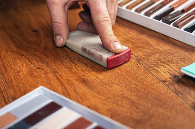 Reparatur und restaurierung von laminat und parkett. kratzer und späne versiegeln. der meister löscht eine funktionierende holzoberfläche.