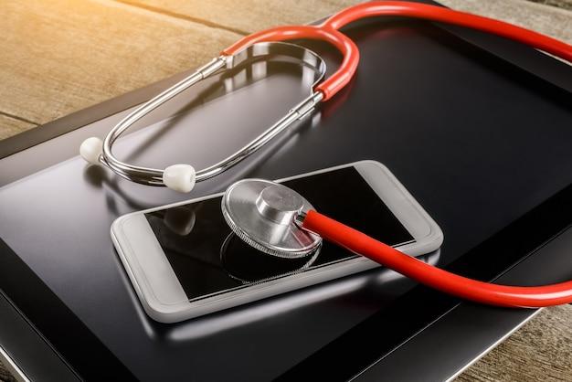 Reparatur- und servicekonzept. digital-tablet und smartphone mit einem stethoskop diagnostiziert