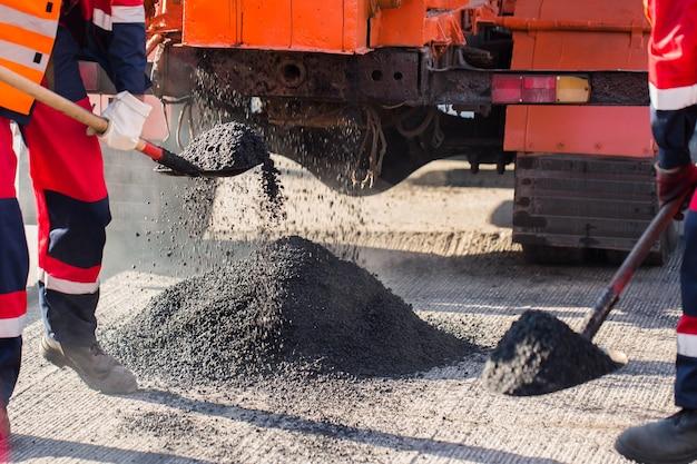 Reparatur von straßen, autobahnen und gehwegen. patchen. das arbeiten mit einer schaufel schläft in der grube ein