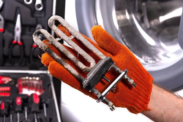 Reparatur von waschmaschinen. hand eines mechanikers mit einer turbulenten elektrischen heizung, die mit einer beschichtung aus hartem wasser bedeckt ist. ersetzen der elektrischen heizung in der waschmaschine