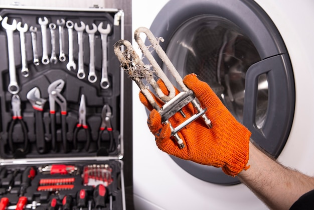Reparatur von waschmaschinen. hand eines mechanikers mit einer turbulenten elektrischen heizung, die mit einer beschichtung aus hartem wasser bedeckt ist.