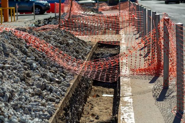 Reparaturarbeiten an der stadtstraße. ein frisch gegrabener graben ist zur sicherheit der bürger mit einem netz eingezäunt.