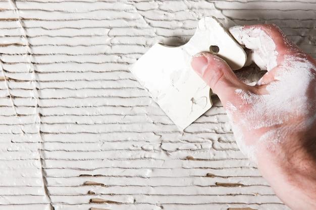 Reparaturarbeiten beim verputzen. hand mit spachtel streicht weißen stuck auf die reliefoberfläche. strukturierter hintergrund mit freiem platz für text aufbauen.