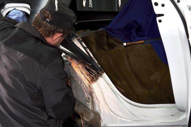 Reparaturarbeiter reparieren beschädigtes auto. arbeiten mit einem winkelschleifer zur befestigung des metallkörpers.