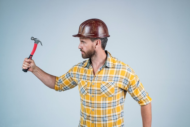 Reparaturen durchführen. mann architekt mit hammer. kerl trägt arbeiteruniform. gut aussehender baumeister im helm. reifer mann trägt kariertes hemd. professioneller konstrukteur oder mechaniker. bauingenieur.