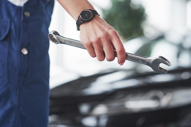 Reparaturfrau ist auf ihrer arbeit. drinnen im autohaus