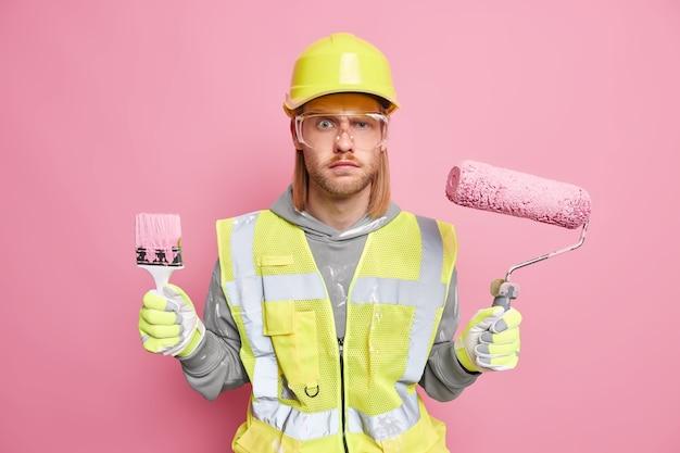 Reparaturkonzept für industrielle arbeiten. seriöser männlicher baumeister auf der baustelle hält bauwerkzeuge trägt schützende sicherheitskleidung, die bereit ist, wände einzeln auf rosafarbener wand zu malen. professioneller mechaniker