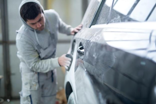 Reparaturmann, der auto für lackierung in werkstatt vorbereitet
