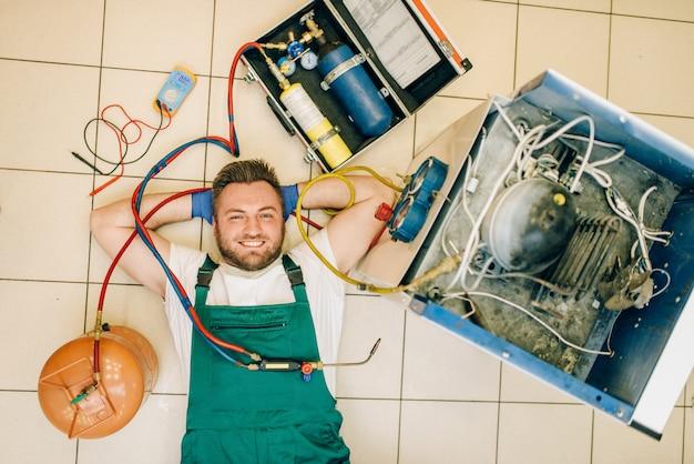 Reparaturmann in uniform liegt in der nähe des kühlschranks zu hause, draufsicht. reparatur der kühlschrankbelegung, professioneller service
