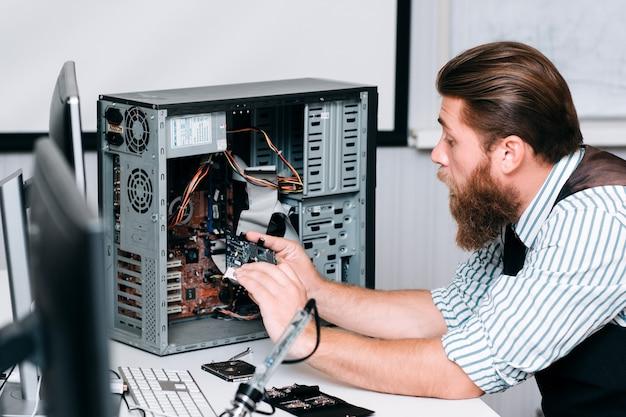 Reparaturmann zerlegt computereinheit zur reparatur. bärtiger mann, der elektronische komponente aus cpu herausnimmt. renovierung, reparatur, baukonzept