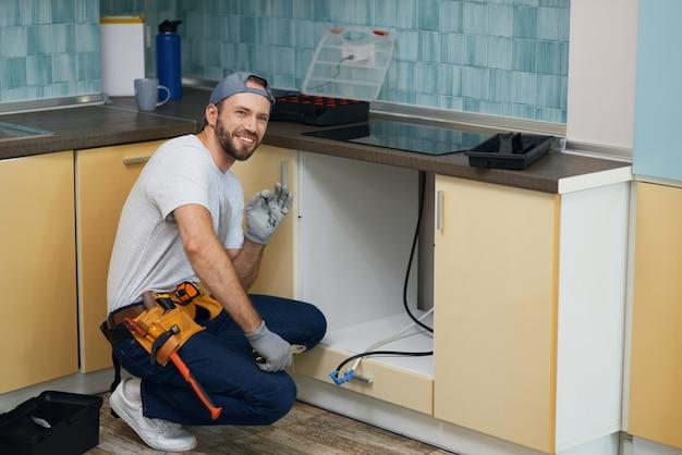 Reparieren sie alles in voller länge von einem fröhlichen jungen klempner, der einen werkzeuggürtel trägt und lächelt, während er ein waschbecken repariert