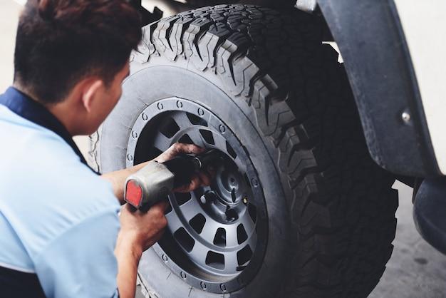 Reparieren sie oder ändern sie den reifenauto-aufnahmemechaniker, der das autorad am reparaturservice abschraubt