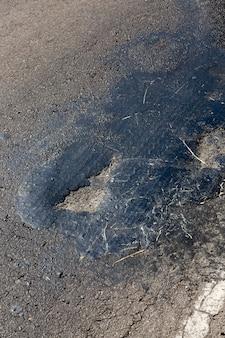 Reparierte straße mit harz und anderen materialien für die straßenreparatur, autospuren auf der straße