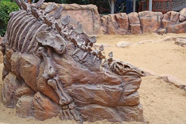 Replikdinosaurierfossil auf dem sandboden