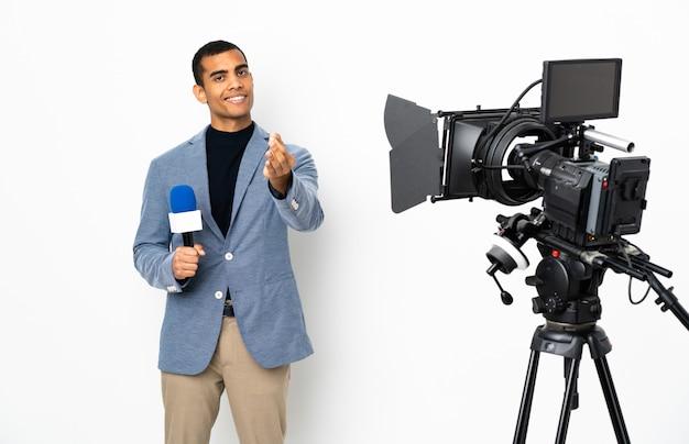 Reporter afroamerikaner mann, der ein mikrofon hält und nachrichten über isolierte weiße wand berichtet, die geldgeste macht
