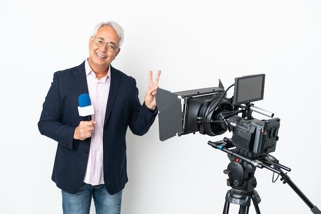 Reporter brasilianischer mann mittleren alters, der ein mikrofon hält und nachrichten isoliert auf weißem hintergrund berichtet, lächelt und zeigt victory-zeichen