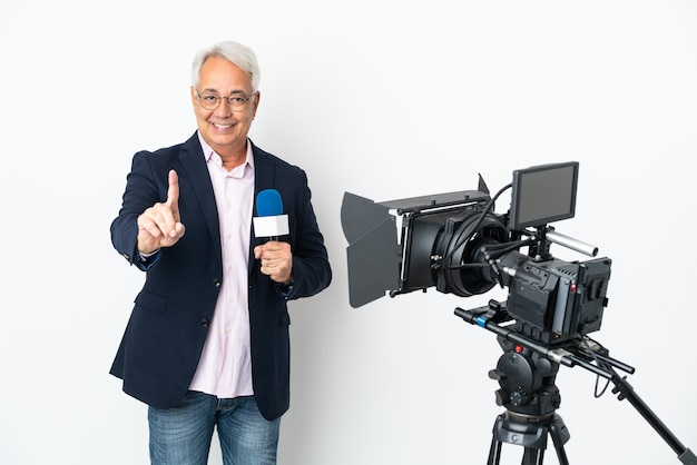 Reporter brasilianischer mann mittleren alters, der ein mikrofon hält und nachrichten isoliert auf weißem hintergrund meldet, die einen finger zeigen und heben