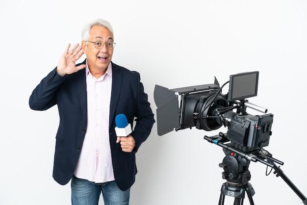 Reporter brasilianischer mann mittleren alters, der ein mikrofon hält und nachrichten isoliert auf weißem hintergrund meldet, indem er etwas hört, indem er die hand auf das ohr legt