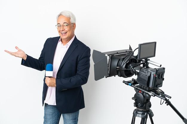 Reporter brasilianischer mann mittleren alters, der ein mikrofon hält und nachrichten isoliert auf weißem hintergrund meldet und die hände zur seite ausstreckt, um einzuladen, zu kommen