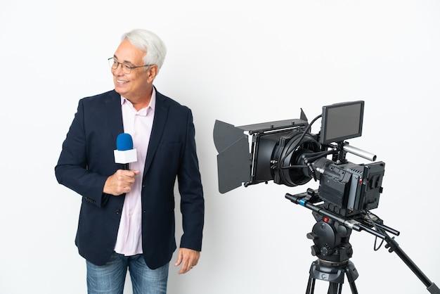 Reporter brasilianischer mann mittleren alters, der ein mikrofon hält und nachrichten isoliert auf weißem hintergrund meldet und zur seite schaut und lächelt
