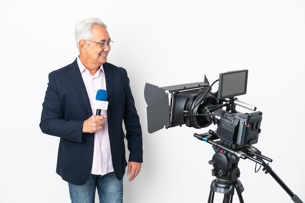 Reporter brasilianischer mann mittleren alters, der ein mikrofon hält und nachrichten isoliert auf weißem hintergrund mit blick auf die seite meldet