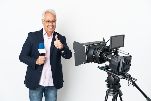 Reporter brasilianischer mann mittleren alters, der ein mikrofon hält und nachrichten isoliert auf weißem hintergrund mit daumen nach oben meldet, weil etwas gutes passiert ist