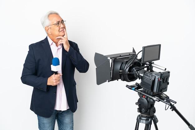 Reporter brasilianischer mann mittleren alters, der ein mikrofon hält und nachrichten isoliert auf weißem hintergrund mit zweifeln meldet