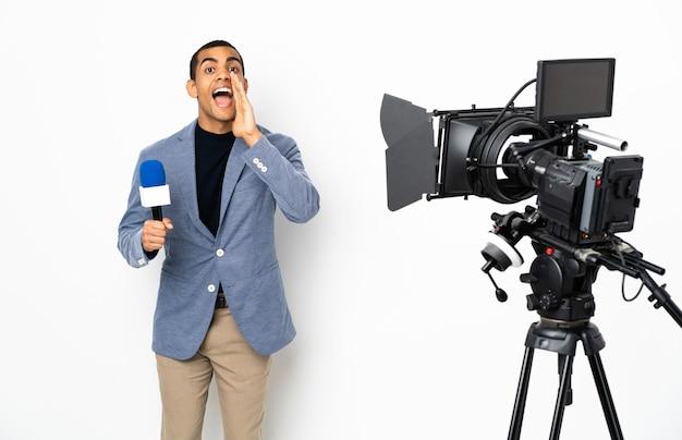 Reporter mann hält ein mikrofon und berichtet nachrichten über isolierte weiße wand schreien und etwas ankündigen