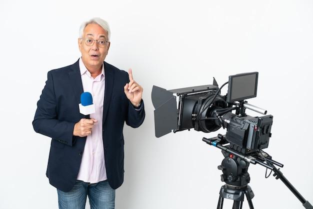 Reporter mittelalter brasilianischer mann, der ein mikrofon hält und nachrichten isoliert auf weißem hintergrund berichtet, um die lösung zu realisieren, während ein finger angehoben wird