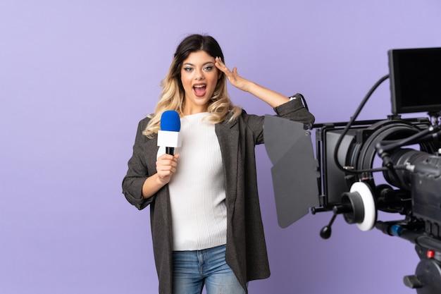 Reporter teenager-mädchen hält ein mikrofon und berichtet nachrichten auf lila wand mit überraschtem ausdruck