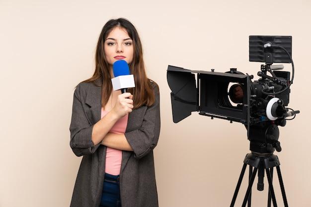 Reporterfrau, die ein mikrofon hält und die nachrichten hält arme gekreuzt meldet