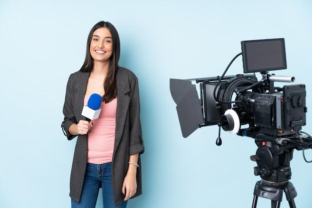 Reporterfrau, die ein mikrofon hält und nachrichten auf blau isoliert berichtet