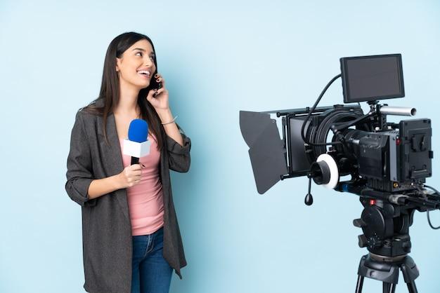 Reporterfrau, die ein mikrofon hält und nachrichten isoliert auf blauer wand berichtet, die ein gespräch mit dem mobiltelefon hält