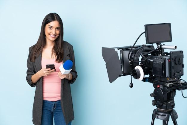 Reporterfrau, die ein mikrofon hält und nachrichten isoliert auf blauer wand meldet, die eine nachricht mit dem handy senden