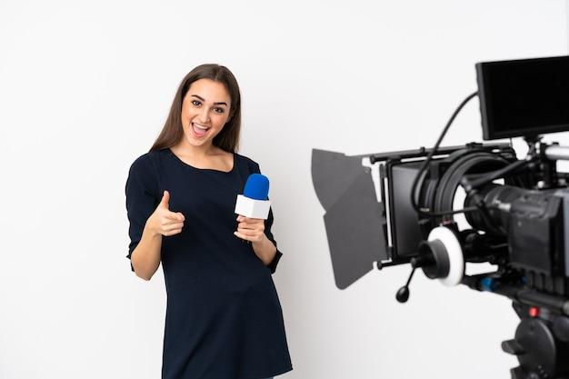 Reporterfrau, die ein mikrofon hält und nachrichten lokalisiert auf weißem hintergrund zeigt, zeigt nach vorne und lächelt