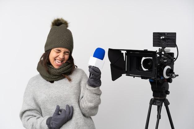 Reporterfrau, die ein mikrofon hält und nachrichten über der lokalisierten weißen wand macht gitarrengeste berichtet