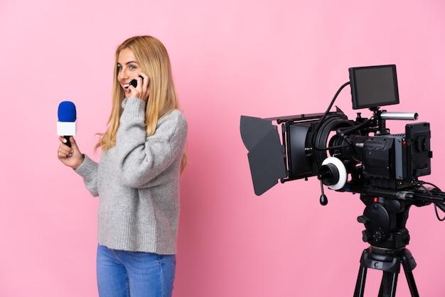 Reporterfrau, die ein mikrofon hält und nachrichten über isolierte rosa wand berichtet, die ein gespräch mit dem mobiltelefon mit jemandem hält