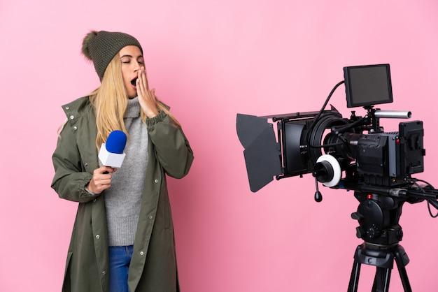 Reporterfrau, die ein mikrofon hält und nachrichten über isolierte rosa wand berichtet, die gähnt und weit geöffneten mund mit hand bedeckt