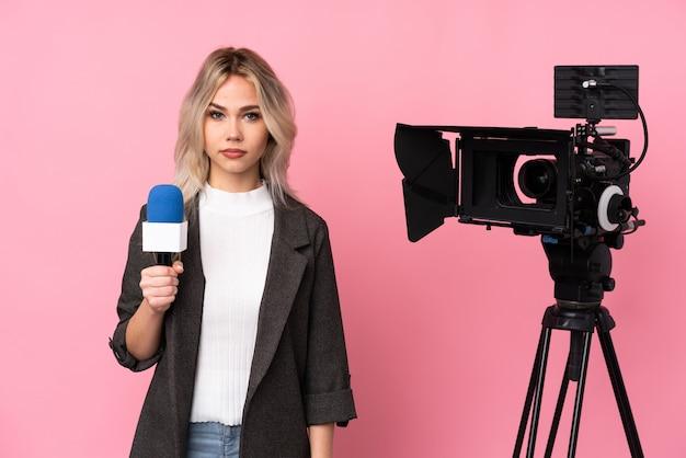 Reporterfrau, die ein mikrofon hält und nachrichten über isolierte rosa wand berichtet