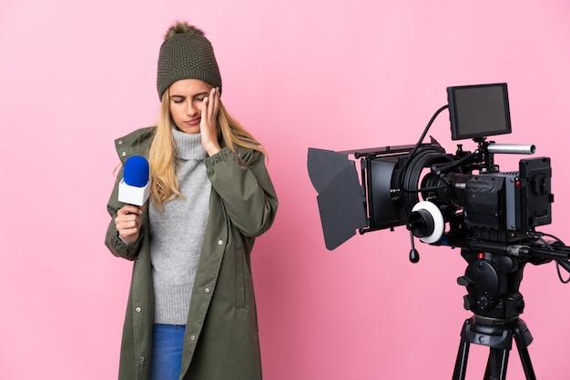 Reporterfrau, die ein mikrofon hält und nachrichten über isolierte rosa wand mit kopfschmerzen berichtet